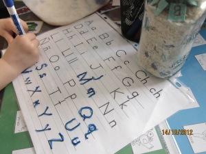 Dry erase marker to trace letters found in sensory box; Rotulador borrable para trazar letars encontradas en la caja sensorial