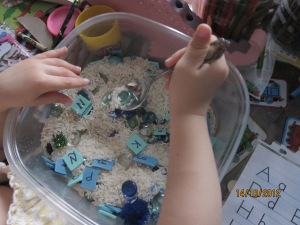 Arroz + letras en trocitos de ¨craft foam¨(¿gomaespuma?) + piedras de cristal azules = caja sensorial del abecedario | rice + letters on pieces of craft foam + blue glass rocks = alphabet sensory tub!
