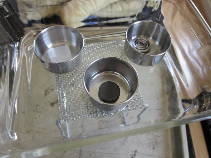 Vista más cercana de materiales de la cuarta demostración: hierro, soldadura, y cera Close-up of the fourth demonstration's materials: iron, solder, and paraffin wax
