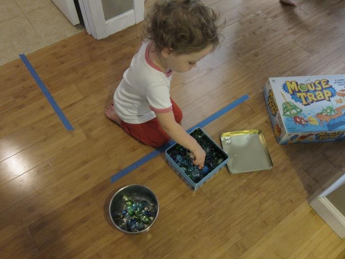 Srta. Corazónvaliente trabajando con las tenacillas, moviendo las piedrecitas de un recipiente a otro.
