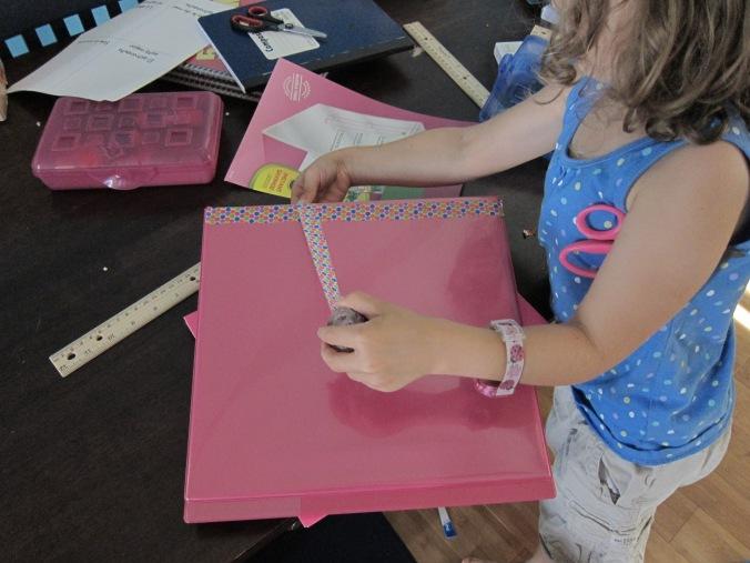 Srta. Aventurera decorando la carpeta con anillos que escogió, con la cinta adhesive que escogió. Preparándose para el comienzo oficial de nuestro año escolar ¡el lunes que viene!